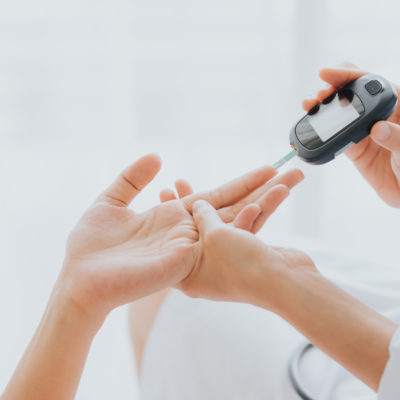 Doctor use glucosmeter checking blood sugar level from patient hand